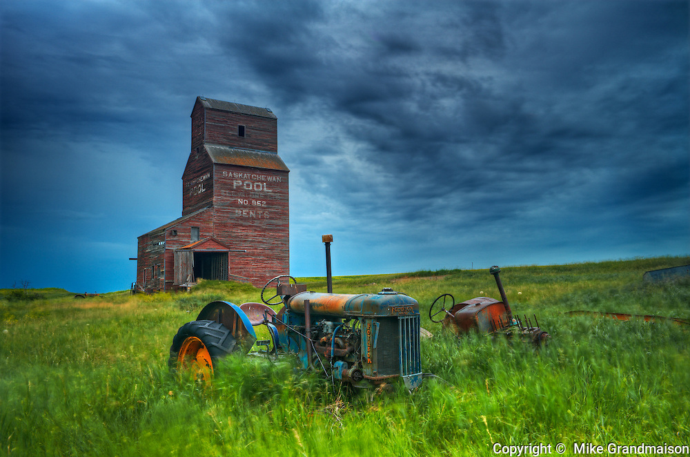 Grain elevators and old tractors in ghost town<br /> Bents<br /> Saskatchewan<br /> Canada