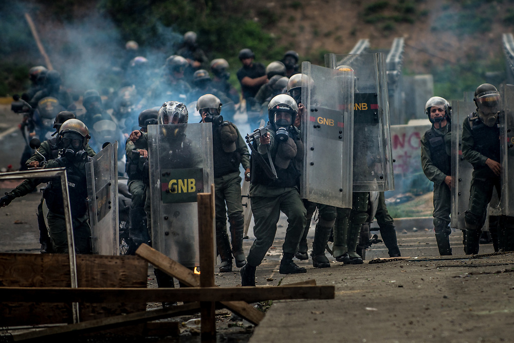CARACAS, VENEZUELA - MAY 24, 2017: National Guard soldiers fire rubber bullets and buckshot at anti-government protesters in Caracas. The streets of Caracas and other cities across Venezuela have been filled with tens of thousands of demonstrators for nearly 100 days of massive protests, held since April 1st. Protesters are enraged at the government for becoming an increasingly repressive, authoritarian regime that has delayed elections, used armed government loyalist to threaten dissidents, called for the Constitution to be re-written to favor them, jailed and tortured protesters and members of the political opposition, and whose corruption and failed economic policy has caused the current economic crisis that has led to widespread food and medicine shortages across the country.  Independent local media report nearly 100 people have been killed during protests and protest-related riots and looting.  The government currently only officially reports 75 deaths.  Over 2,000 people have been injured, and over 3,000 protesters have been detained by authorities.  PHOTO: Meridith Kohut
