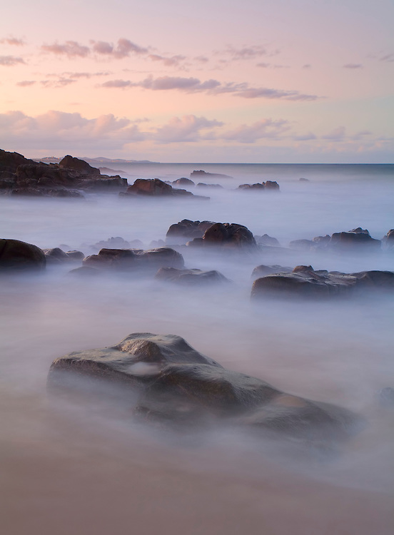The last dusky pinks of the day and the soft blur of water captured together with the bold rocks create an easy and enchanting scene.