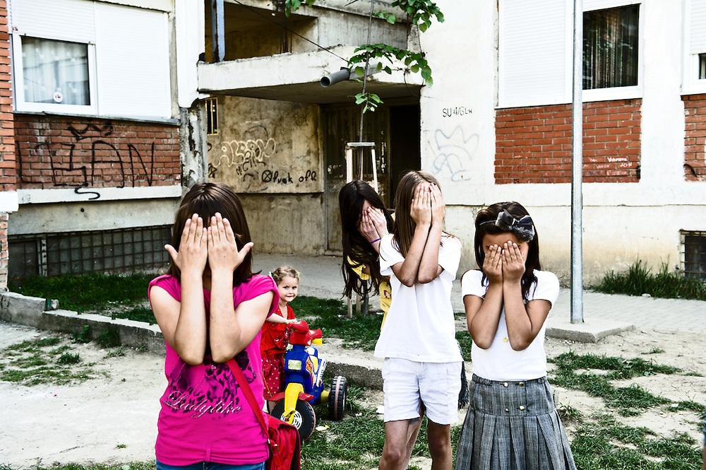 Bambine nella zona periferica di Pristina, Repubblica del Kosovo, 2012<br /> <br /> 3 giugno 2004<br /> La maggior parte della gente che incontro &egrave; di sesso maschile. Uomini che lavorano o bevono caff&egrave; al bar. Mi chiedono di fotografarli o di fare due chiacchiere. Comunicare non &egrave; un problema. Parlo italiano e mi capiscono. Ho conosciuto un ragazzo che ha la moglie in inghilterra. Non la vede da 6 mesi. Era tornato in Kosovo per rinnovare il visto e gli &egrave; stato rifiutato. Nel frattempo la moglie ha fatto un incidente ed ora &egrave; invalida.<br /> <br /> Ho parlato con gente dell'ONU. Tutti parlano di quello che &egrave; successo lo scorso 13 marzo, delle manifestazioni, della distruzione di un edificio nel centro di Pristina abitato da kosovari serbi, dell'incendio di un edificio religioso. I kosovari albanesi reputano i serbi responsabili della morte di 3 ragazzi.