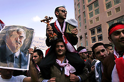 A demonstrator shows the unity of the people in their anger against Syria by holding a cross and the Koran, Beirut, Lebanon, Feb. 21, 2005. Several thousand Lebanese gathered at the scene of the bombing that killed former Prime Minister Rafik Hariri, afterward they walked to his grave.