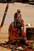 Himba woman sitting on a rug in the desert smoking a pipe in Namibia, Africa. Fine art photography prints, wall art and stock images.