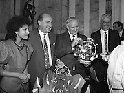 Vietnamese Refugees are Naturalised.  (R61)..1987..08.07.1987..07.08.1987..8th July 1987..A large group of Vietnamese refugees were presented with certificates of naturalisation by Justice Minister, Gerard CollinsTD at the dept of Foreign Affairs in Iveagh House today. The vietnamese were dispossed due to the Vietnam war.The group ,consisting of 156 adults, arrived in Ireland from Vietnam and some refugee camps inHong Kong and Malaysia...Image shows Minister Gerard Collins  and officials accepting gifts of flowers at the ceremony in Iveagh House.