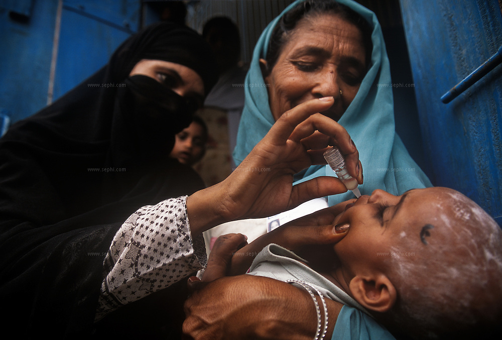 A burkha clad vaccinator giving the drops to a child in the Karula district in Moradabad city. Moradabad has the highest number of polio cases of any district in India. The area's Muslim population had shown resistance to the project but now most of the resistance is over and only a few families are still refusing to take the vaccine.