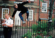 G.B. ENGLAND. London. A boy jumps away after police questioning, on the streets around Lambeth Walk. 2002.