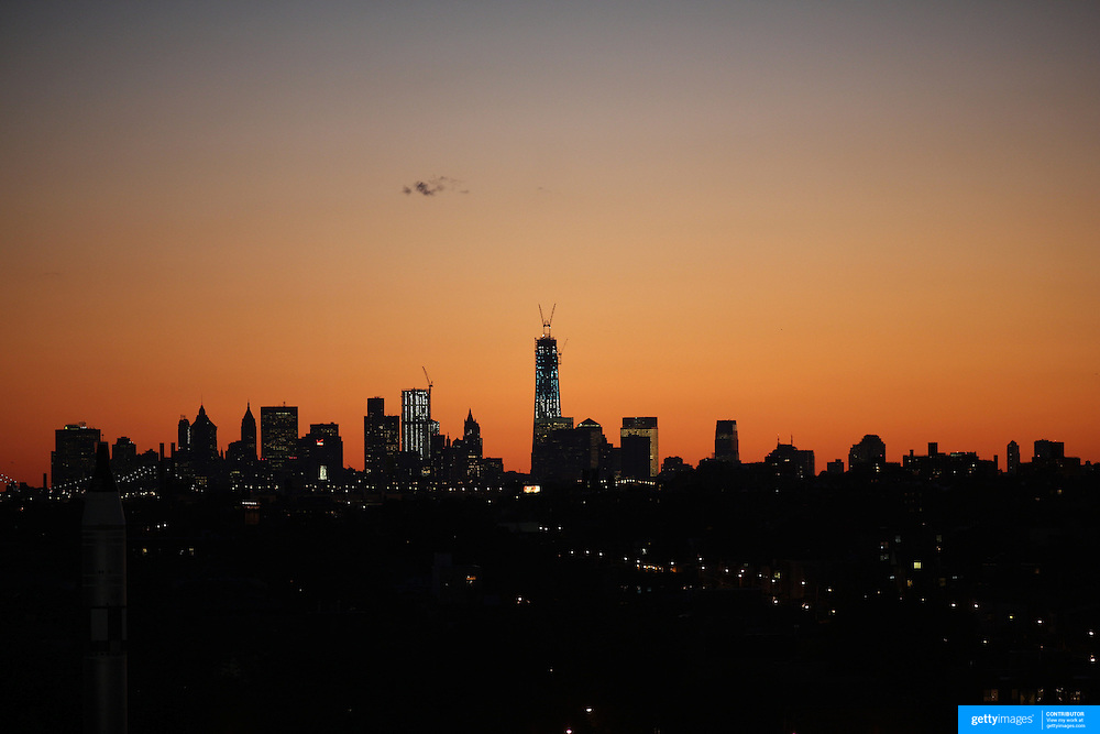 The sun sets behind the Manhattan skyline showing the rising frame of One World Trade Center in lower Manhattan in New York City viewed from Arthur Ashe Stadium  during the US Open Tennis Tournament, Flushing, New York. USA. 10th September 2012. Photo Tim Clayton