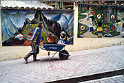 PERU, AGUAS CALIENTES:  Workman pushing a wheelbarrow in front of murals painted on the walls of Aguas Calientes, the town closest to Machu Picchu in the Urubamba Valley of Peru.