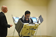 Poll workers Matt Moore (left) and Keith Cain (right) run to make sure voting machines don't fall over as Prabhakar Mantena trips over a cord after voting at the Oxford Conference Center in Oxford, Miss. on Tuesday, November 6, 2012.