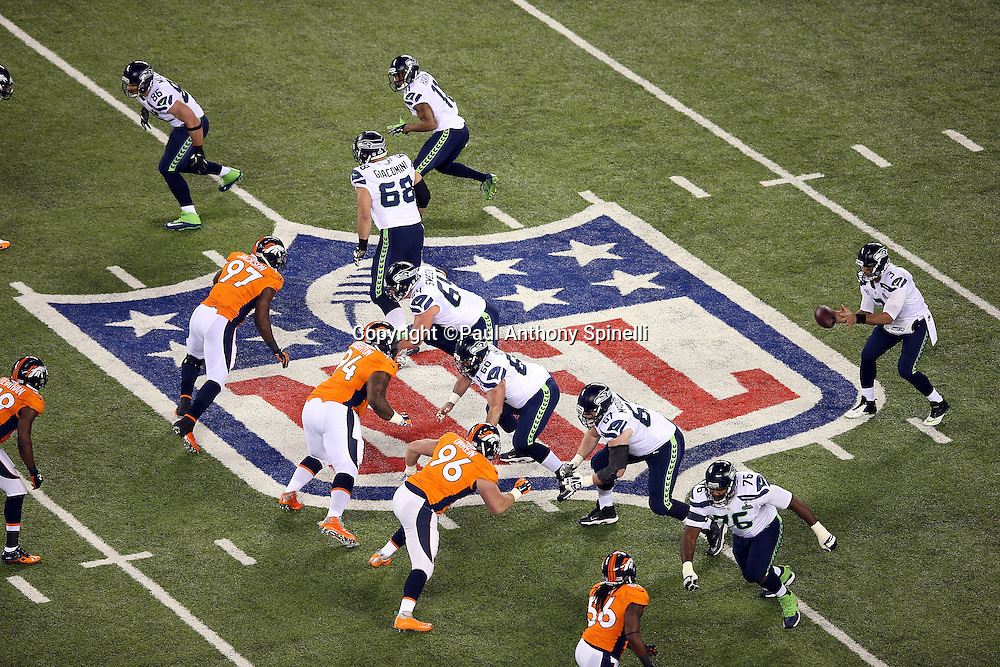 Seattle Seahawks quarterback Russell Wilson (3) catches a shotgun snap as the teams grapple while standing on the NFL logo painted on the field during the NFL Super Bowl XLVIII football game against the Denver Broncos on Sunday, Feb. 2, 2014 in East Rutherford, N.J. The Seahawks won the game 43-8. ©Paul Anthony Spinelli