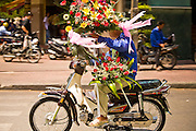 09 MARCH 2006 - HO CHI MINH CITY, VIETNAM: A flower vendor making a delivery by motorcycle in Ho Chi Minh City (formerly Saigon) Vietnam. Photo by Jack Kurtz