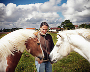 Nathalie Bertranine, 32, feed horses outside her Montagnès farm, on Tuesday, May 11, 2010, in Came, France. Nathalie Bertranine took over the farm in 2005 when her parents retired. She began by refurbishing the farm's large barn into modern stables and a riding ring. That allows Bertranine to serve tourists ready to pay for horseback excursions in the surrounding countryside, and run a popular equestrian club for locals.