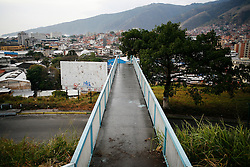 A bridge leads across the main street that circles the 23 de Enero barrio in Caracas, seen in the background is El Avila mountain.
