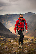Walker crossing Broad Crag with Great Gable beyond, Wasdale, Scafell, Lake District, Cumbria, Uk