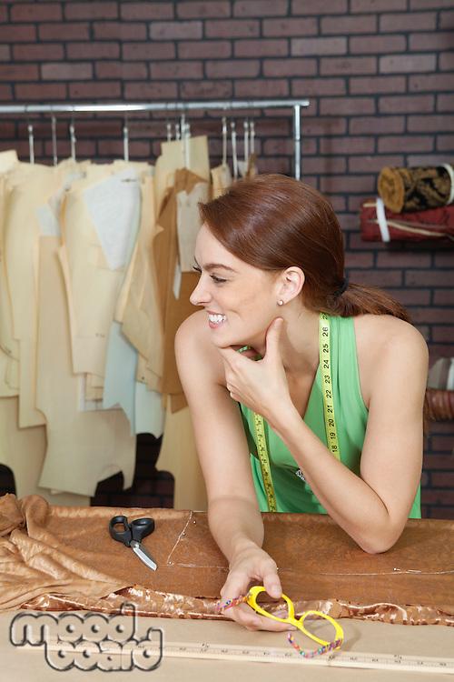 Happy female fashion designer looking away while holding eyeglasses