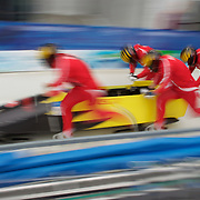 "Winter Olympics, Vancouver, 2010.The Switzerland team at the start during the Bobsleigh Four-man competition  at The Whistler Sliding Centre, Whistler, during the Vancouver Winter Olympics. 26th February 2010. Photo Tim Clayton..'BOB'..Images from the Four-man Bobsleigh Competition. Winter Olympics, Vancouver 2010..History was made at the Whistler Sliding Centre when the USA four-man bobsleigh team, led by Steven Holcomb took the Gold. The first time since 1948, a gap of 62 years, since the USA have won an Olympic Bobsleigh gold and they did it with their sleigh named ""Night Train""...The four days of practice and competition show the tension, nervousness and preparation as the teams of hardened men cope with the challenge of traveling at average speeds of over 150 km an hour. Indeed, five teams had already pulled out of the event before the opening heats because of track complexity, speed and fear, and on the final day, another four teams did not start after six crashes in the first two heats...Teams warm up behind the start complex, warming muscles in the cold in preparation for the explosive start. Many teams prepare in silence, mentally preparing themselves as they wait at the top of the run, in the bobsleigh sheds and the loading areas for their turn. When it's time to slide each team performs it's own starting ritual, followed by the much practiced start out of the blocks for just over four seconds, the teams are then in the hands of the accomplished drivers as they hurtle down the track for just over fifty seconds...Spectators clamber for the best position on track to see the sleighs for a split second, many unsuccessfully try to capture the moments on camera, The rumble of the sleigh is heard then the crowds gasp as it hurtles past in a blur...The American foursome of  Steven Holcomb, Justin Olsen, Steve Mesler and Curtis Tomasevicz finished with a pooled four-heat time of 3min 24.46sec. The German team led by Andre Lange won the Silver Medal in a combined ti"