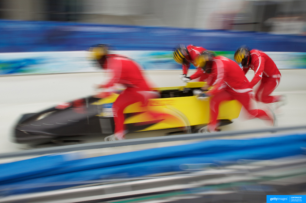 """Winter Olympics, Vancouver, 2010.The Switzerland team at the start during the Bobsleigh Four-man competition  at The Whistler Sliding Centre, Whistler, during the Vancouver Winter Olympics. 26th February 2010. Photo Tim Clayton..'BOB'..Images from the Four-man Bobsleigh Competition. Winter Olympics, Vancouver 2010..History was made at the Whistler Sliding Centre when the USA four-man bobsleigh team, led by Steven Holcomb took the Gold. The first time since 1948, a gap of 62 years, since the USA have won an Olympic Bobsleigh gold and they did it with their sleigh named """"Night Train""""...The four days of practice and competition show the tension, nervousness and preparation as the teams of hardened men cope with the challenge of traveling at average speeds of over 150 km an hour. Indeed, five teams had already pulled out of the event before the opening heats because of track complexity, speed and fear, and on the final day, another four teams did not start after six crashes in the first two heats...Teams warm up behind the start complex, warming muscles in the cold in preparation for the explosive start. Many teams prepare in silence, mentally preparing themselves as they wait at the top of the run, in the bobsleigh sheds and the loading areas for their turn. When it's time to slide each team performs it's own starting ritual, followed by the much practiced start out of the blocks for just over four seconds, the teams are then in the hands of the accomplished drivers as they hurtle down the track for just over fifty seconds...Spectators clamber for the best position on track to see the sleighs for a split second, many unsuccessfully try to capture the moments on camera, The rumble of the sleigh is heard then the crowds gasp as it hurtles past in a blur...The American foursome of  Steven Holcomb, Justin Olsen, Steve Mesler and Curtis Tomasevicz finished with a pooled four-heat time of 3min 24.46sec. The German team led by Andre Lange won the Silver Medal in a combined ti"""