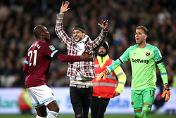 West Ham United's Angelo Ogbonna stops a pitch invader during the Carabao Cup, Fourth Round match at the London Stadium.