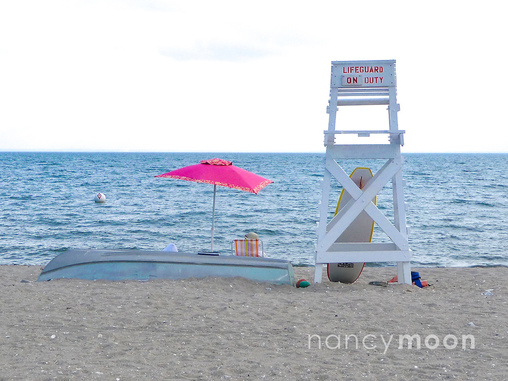 The beach with lifeguard chair and umbrella.<br />