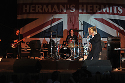 Peter Noone holding an old album cover of his likeness in front of his face while singing at the Hamden Free Summer Concert Series, July 2009.