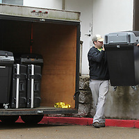 Lee County Employees Luke Franks and Tyler Lucas lift a voting machine off the loading dock at the Lee County Justice Center as they load up for Lee County District 1 on Monday morning in Tupelo.
