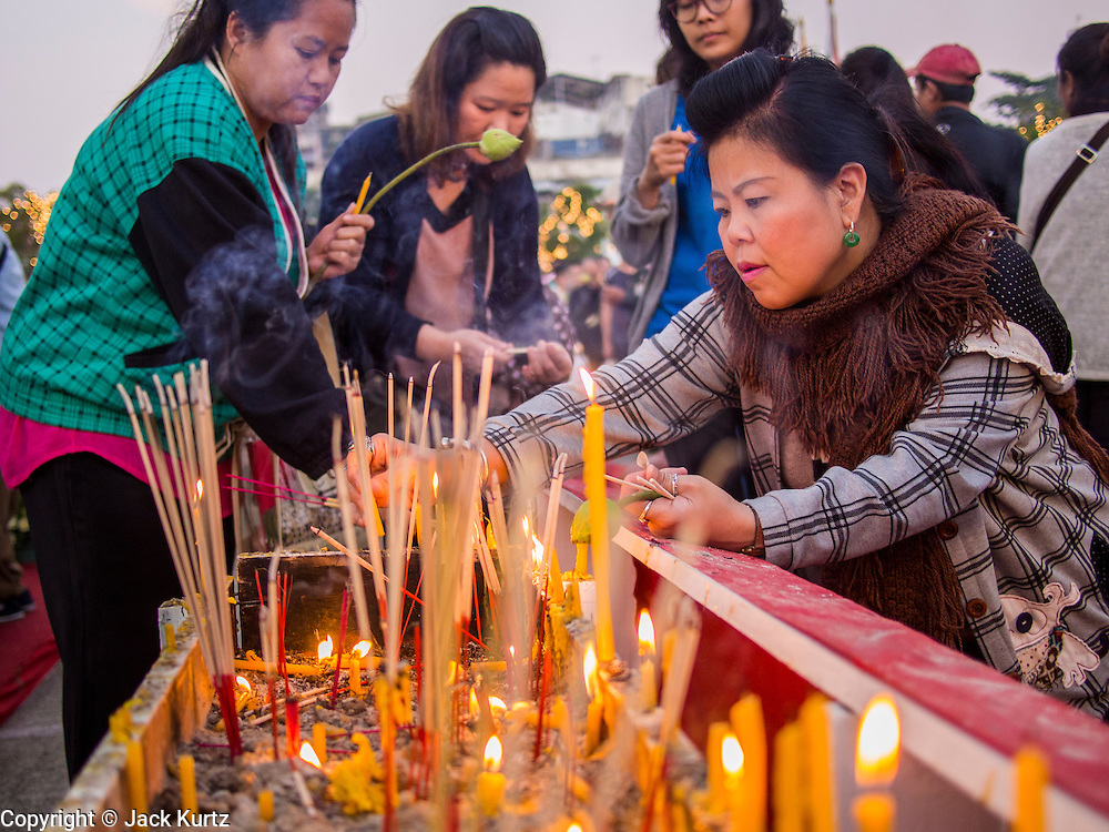 01 JANUARY 2014 - BANGKOK, THAILAND: People light candles and pray in front of Bangkok City Hall. Several thousand people, mostly Bangkok city officials, gathered on the plaza of Bangkok City Hall Wednesday for the traditional New Year merit making ceremony.     PHOTO BY JACK KURTZ