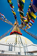 Prayer flags stretched from the top of the Boudhanath stupa, cast shadows on the side of the white stupa in Kathmandu, Nepal.