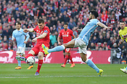 Liverpool midfielder James Milner (7) with a shot during the Capital One Cup match between Liverpool and Manchester City at Anfield, Liverpool, England on 28 February 2016. Photo by Simon Davies.