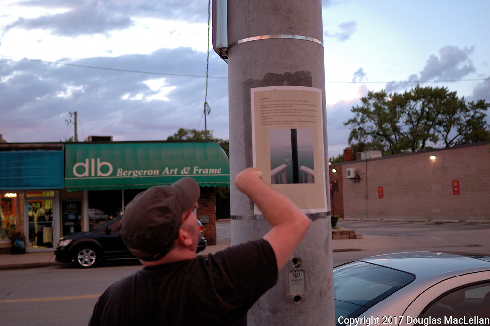 CANADA, Windsor. May, 2017. Jeff Noonan, a professor and artist, places posters on poles through out Windsor as part of Douglas MacLellan and his poster art project for MayWorks Windsor 2017. MayWorks is a labour arts festival.