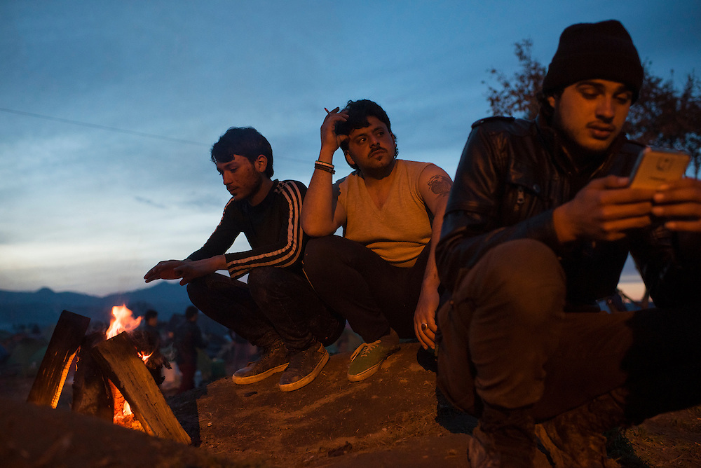 Syrians warm themselves by a campfire as night falls at a refugee camp on the Macedonian (FYROM) border on March 8, 2016 in Idomeni, Greece.