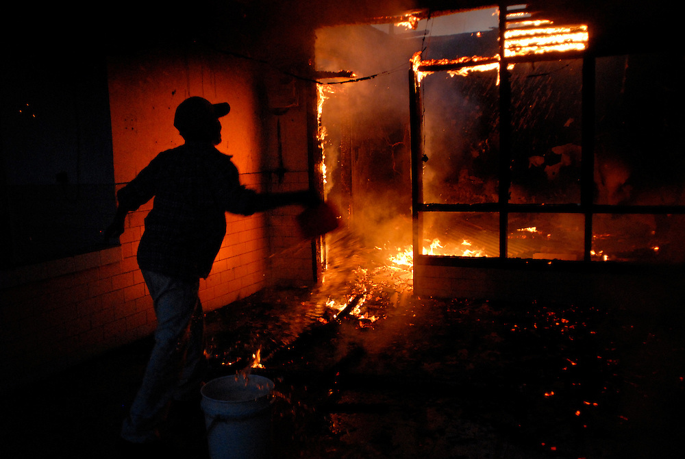 A man throws water from a bucket onto a raging fire, as yet another building go up in Dili, East Timor 05/06/06