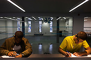Young men study at workstations in communal area at London Metropilitan University's Holloway Road campus.
