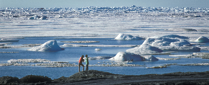 Two boys play near the summer ice pack on the Arctic Ocean in the Iñupiat village of Barrow, Alaska.
