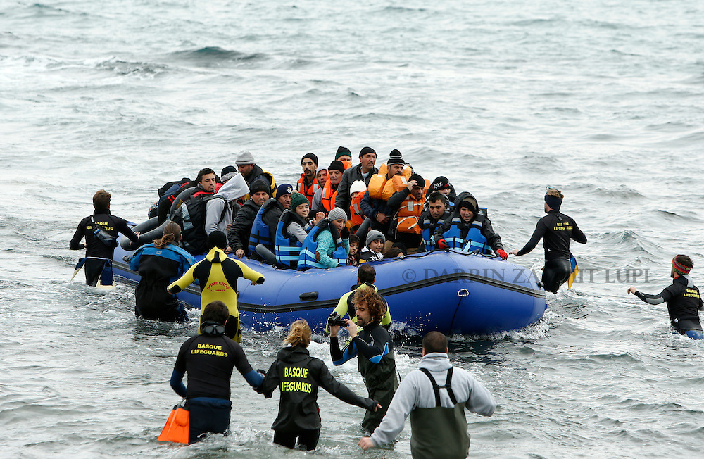 Volunteers approach a rubber dinghy packed with refugees and migrants as they arrive on a beach on the Greek island of Lesbos, January 29, 2016. Photo: Darrin Zammit Lupi
