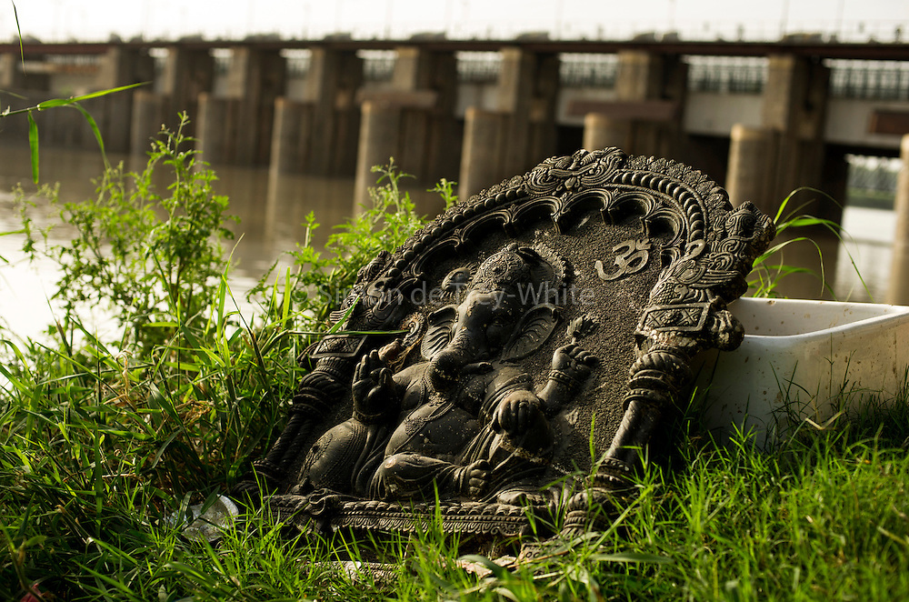 21st August 2014, Yamuna River, New Delhi, India. A bas-relief representation of the Hindu deity Ganesha near a shrine on the banks of the Yamuna River, New Delhi, India on the 21st August 2014. In Hinduism the elephant-headed god Ganesh, the remover of obstacles, is invoked before every new endeavour and is particularly revered by all Hindus. <br /> <br /> Elephant handlers (Mahouts) eke out a living in makeshift camps on the banks of the Yamuna River in New Delhi. They survive on a small retainer paid by the elephant owners and by giving rides to passers by. The owners keep all the money from hiring the animals out for religious festivals, events and weddings, they also are involved in the illegal trade of captive elephants.The living conditions and treatment of elephants kept in cities in North India is extremely harsh, the handlers use the banned 'ankush' or bullhook to control the animals through daily beatings, the animals have no proper shelters are forced to walk on burning hot tarmac and stand for hours with their feet chained together. <br /> <br /> PHOTOGRAPH BY AND COPYRIGHT OF SIMON DE TREY-WHITE<br /> + 91 98103 99809<br /> email: simon@simondetreywhite.com photographer in delhi