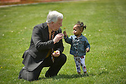 At the edge of the May 4 commemoration, KSU asst. director of public safety, Bill Buckbee, exchanges dandelions with a young attendee.