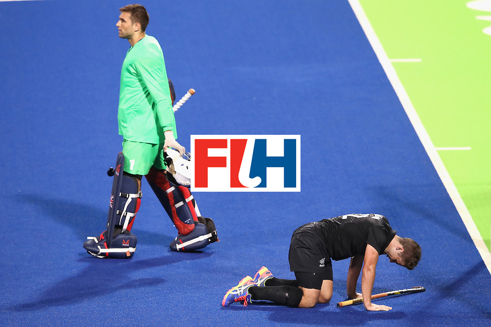 RIO DE JANEIRO, BRAZIL - AUGUST 07:  George Pinner of Great Britain walks away as Nick Wilson New Zealand tries to get to his feet after a heavy collision during the men's pool A match between Great Britain and New Zealand on Day 2 of the Rio 2016 Olympic Games at the Olympic Hockey Centre on August 7, 2016 in Rio de Janeiro, Brazil.  (Photo by Mark Kolbe/Getty Images)