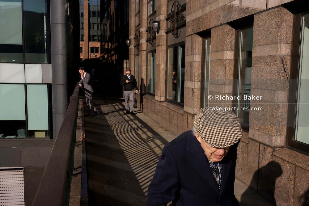 Elderly man walks along modern walkway, past a youthful office worker enjoying a thoughful moment in City of London.