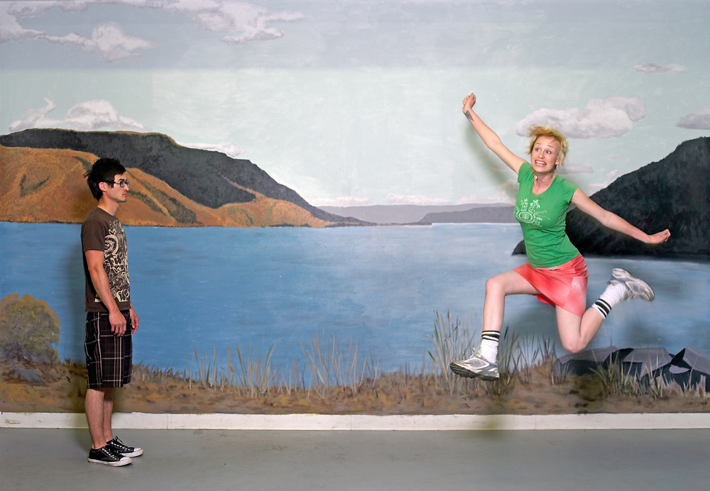 30's something man glaring at woman jumping in front of landscape mural.