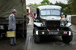 © Licensed to London News Pictures. <br /> 16/10/2016. <br /> Goathland, UK.  <br /> <br /> A man dressed in a 1940's period suit waits for a military convoy to pass at Goathland station during the final day of the North Yorkshire Moors Railway Wartime Weekend event. <br /> The annual event brings together re-enactors and enthusiasts along the length of the NYMR heritage steam railway line to recreate the feel of the war years of the 1940's. <br /> <br /> Photo credit: Ian Forsyth/LNP