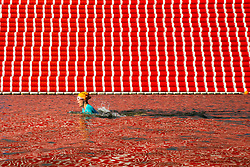 Journalist Isabelle Hardman at the Serpentine's lido swims past artist Christo's 20m high installation on The Serpentine made from over 7000 barrels, titled The Mastaba, which will be on the Serpentine until 23 September 2018. The Installation is comprised of 7,506 horizontally stacked barrels. It is 20m high, 30m wide and 40m long. Hyde Park, London, June 18 2018.