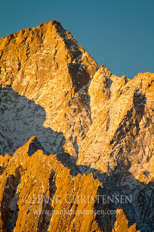 Shadow plays against the bright orange rock of sunrise, as Lone Pine Peak glows at dawn