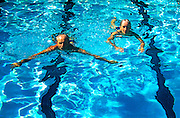 Senior couple swimming laps in a pool.