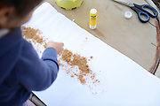 Child's handcraft glueing sand on paper
