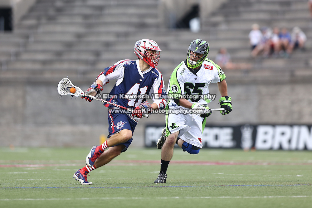 Mike Stone #41 of the Boston Cannons runs with the ball past Mike Unterstein #65 of the New York Lizards during the game at Harvard Stadium on July 19, 2014 in Boston, Massachusetts. (Photo by Elan Kawesch)
