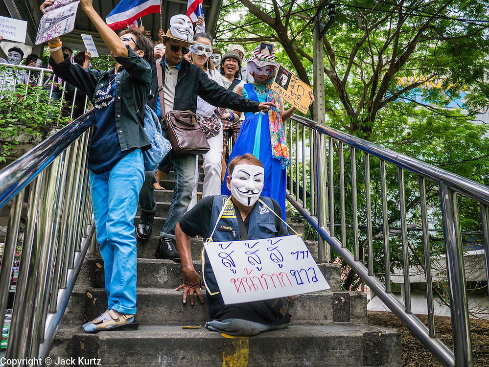 """02 JUNE 2013 - BANGKOK, THAILAND: A legless man leads a protest march down a flight of stairs through the Bangkok skywalk system. About 300 people wearing the Guy Fawkes mask popularized by the movie """"V for Vendetta"""" and Anonymous, the hackers' group, marched through central Bangkok Sunday demanding the resignation of Prime Minister Yingluck Shinawatra. They claim that Yingluck is acting as a puppet for her brother, former Prime Minister Thaksin Shinawatra, who was deposed by a military coup in 2006 and now lives in exile in Dubai.      PHOTO BY JACK KURTZ"""