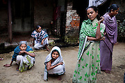 """(L-R: (blue) Saraswati Saha, 84; unnamed; (white) Kamla Das, 90; (green) Purnima Mandol, 36; and unnamed) Elderly women who were the original refugees of The Partition gather and discuss their unfortunate situation outside their homes in Cooper's Camp, Nadia district, Ranaghat, North 24 Parganas, West Bengal, India, on 19th January, 2012. """"They dropped us off here (over six decades ago) and I'm still here!"""" says Kamla Das. """"We would never want to go back to Bangladesh."""" Over 60 years after the bloody creation of Bangladesh in 1947, refugees who fled what was then known as West Pakistan to India still live as refugees, standing in line for government handouts..Photo by Suzanne Lee for The National (online byline: Photo by Szu for The National)"""