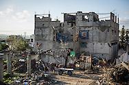 A horse waits next to a building hit by many bullets in Shejaiya