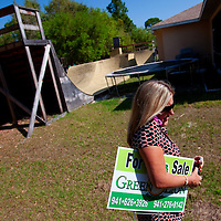 TAMPA, FL -- March 22, 2011 -- Shannon Moore, broker/owner of Green Lion Realty, picks up a sign for a home that sold in North Port, Fla., 2011.  A recent study showed that one and five homes in the state of Florida is vacant.