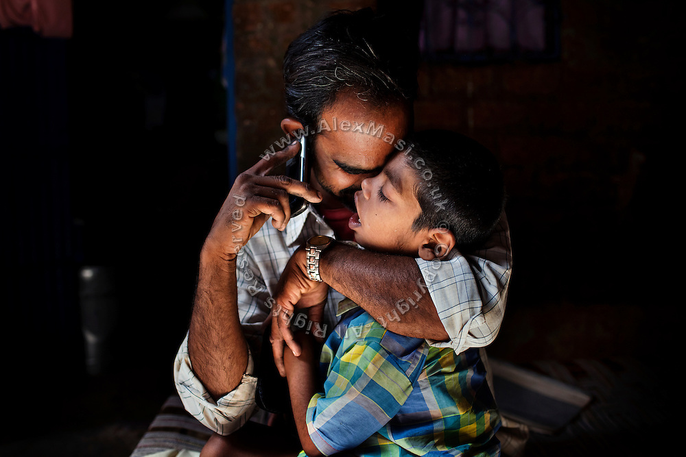 Rashid Ali, 35, a '1984 Gas Survivor', is talking on a mobile phone while hugging his disabled son Rahil Ali, 7, a boy affected by lissencephaly, inside their home in Bhopal, central India, near the abandoned Union Carbide (now DOW Chemical) industrial complex. Rahil lives with his father and deaf grandmother in a small, single room rented within a larger house. Due to the hardship and stigma associated to birth defects in India, in 2009 Rahil's mother left the family.