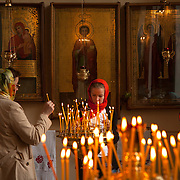 Lighting candles in Vladimirskaya Church in Saint Petersburg, Санкт-Петербург, the second largest city in Russia, located on the Neva River near the Baltic Sea.<br /> Photography by Jose More